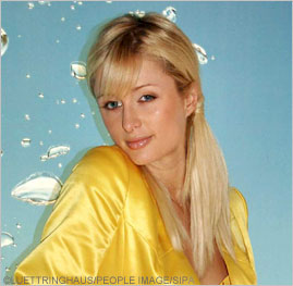 Paris Hilton, in a bright yellow silk or satin blouse.
